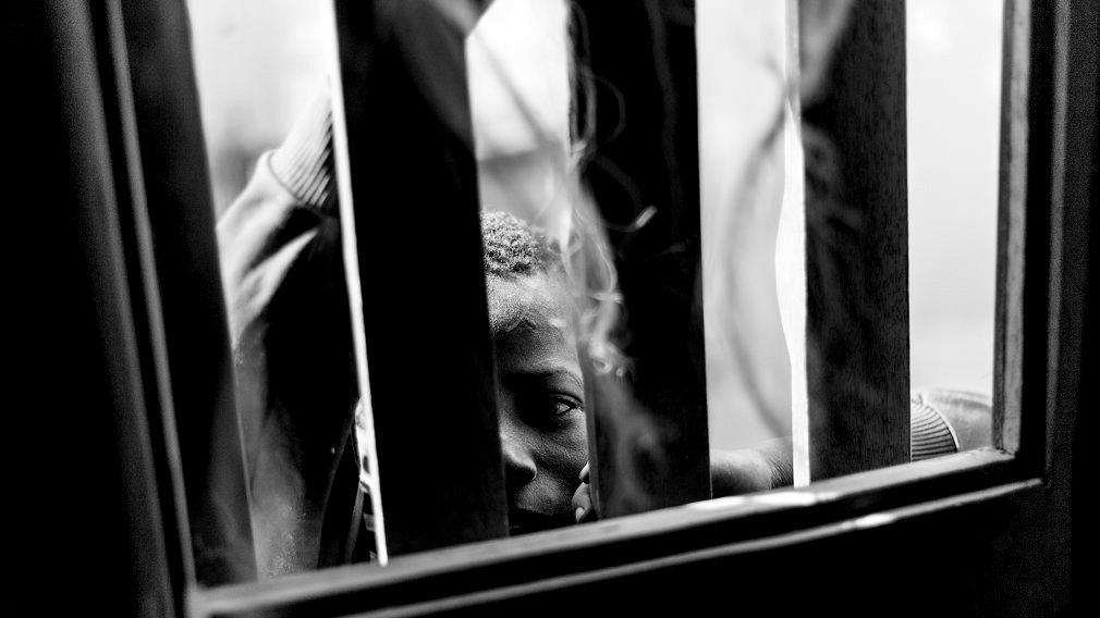 Un niño talibé observa a través de una ventana con rejas. La educación de los talibés está basada en amenazas, violencia y castigos. Los niños sufren desde golpes y latigazos hasta la privación de libertad por varios días o semenas y en ocasiones atados con cuerdas y grilletes. IÑIGO ALZUGARAY