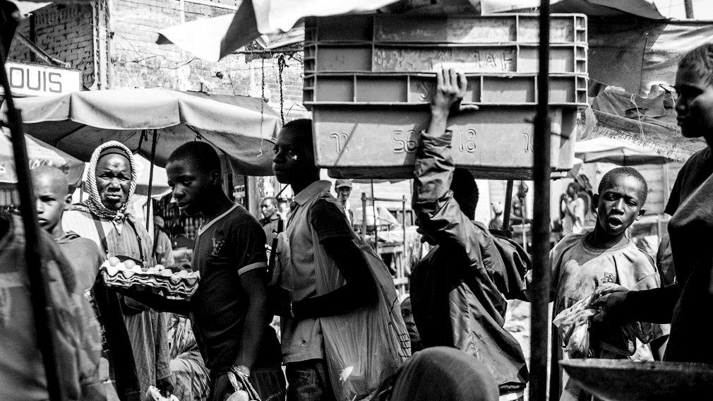 Un talibé carga con varias cajas en el mercado de Saint Louis. Es habitual que estos niños sean utilizados como animales de carga en los mercados, donde soportan pesos muy superiores a los recomendados para su edad. En ocasiones reciben alguna limosna por su trabajo pero en otras no. IÑIGO ALZUGARAY