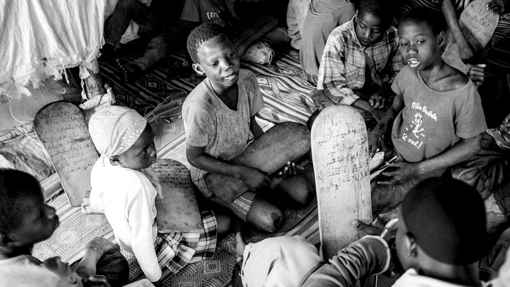 Varios niños y una niña repasan la lección del Corán con su maestro coránico, el marabú, en una daara de Saly Velingara. En las escuelas coránicas, llamadas daaras, pueden vivir hacinados más de 50 niños talibés, que son entregados por sus familias a los marabúes para que los eduquen en el estudio del Corán. Aunque la mayoría son niños, también existen niñas talibés. IÑIGO ALZUGARAY