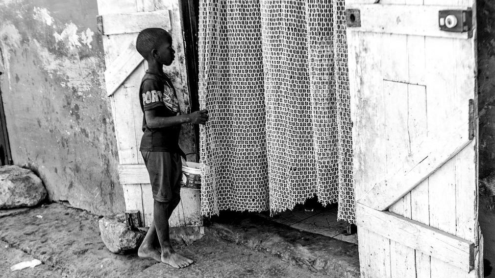 Un niño talibé mendiga a las puertas de una casa en Saint Louis. Los niños son confiados a un maestro coránico que les acoge para enseñarles el corán, pero las condiciones de vida en las que se encuentran son inhumanas y son obligados a pedir dinero por las calles bajo amenaza de violencia física y mental. Sólo en Saint Louis, hay alrededor de 15.000 niños talibés. IÑIGO ALZUGARAY