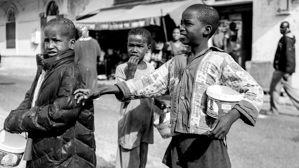 Unos niños talibés, con los típicos botes de tomate que utilizan para mendigar,  piden limosna en las calles de Saint Louis. Los niños son obligados a mendigar a diario en beneficio de su maestro del Corán. El marabú es el tutor del niño mientras esté en la daara y es su responsabilidad alimentarlo y cuidarlo, cosa que no hace en la práctica. IÑIGO ALZUGARAY