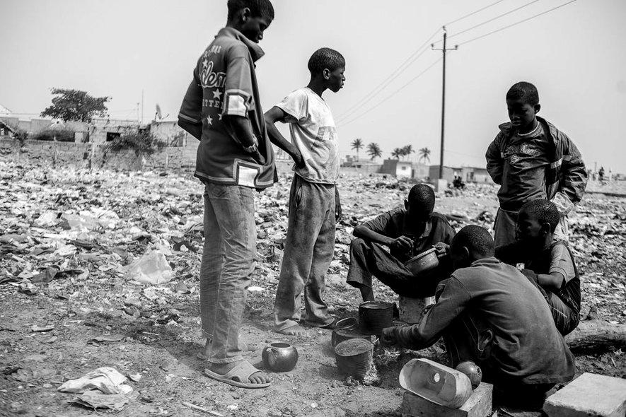 Varios talibés cocinan y comen rodeados de basura en el exterior de su daara en Saint Louis. La mayoría de los niños talibés sufren hambre y desnutrición por el mal cuidado por parte de su marabú, que utiliza el dinero de las limosnas para beneficio propio en lugar de para el cuidado de los niños. IÑIGO ALZUGARAY