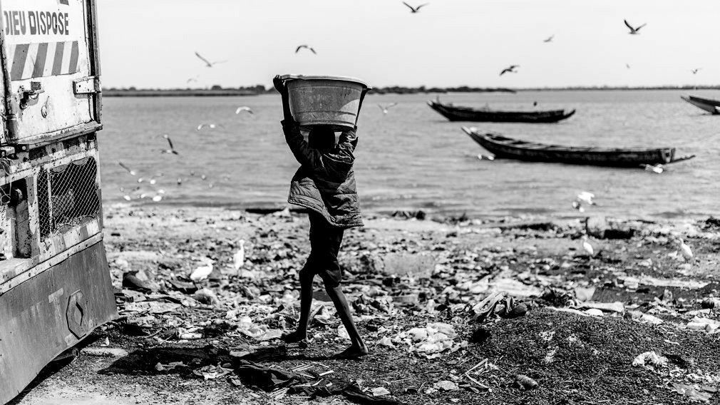 Un niño talibé carga con un balde en las orillas del Río Senegal en Saint Louis. Los niños talibés suelen ser obligados a cargar pesos muy superiores a los recomendados para su edad y es habitual que estén rodeados de entornos insalubres y llenos de basura. IÑIGO ALZUGARAY